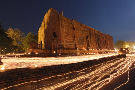 candle light trail of Buddhism Ceremony at temple ruin at dusk o