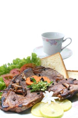 Photo pour Gros plan de se t OS poivre steak habiller de légumes et de pain avec la tasse à café - image libre de droit