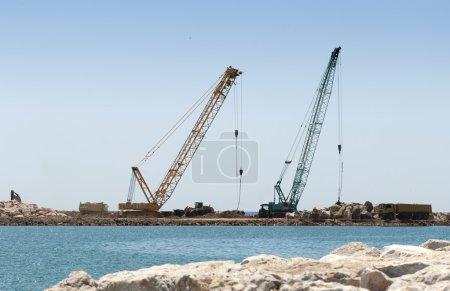 Building a dike. Cranes and excavator put stones