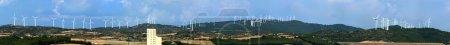 Panoramic image of wind turbines on the ridge of a mountain