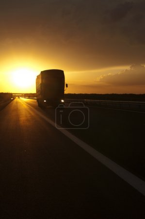 Truck traveling at sunset
