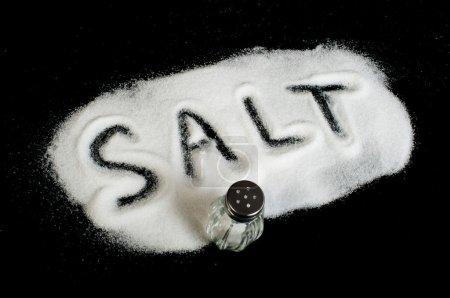 Photo for Word Salt on black background written by spilled salt - Royalty Free Image