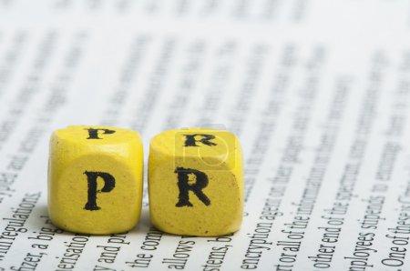 Photo pour Mot PR.Cubes en bois sur le journal. Gros plan plan studio - image libre de droit