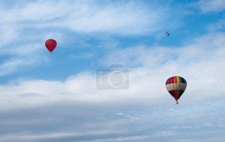 Photo pour Ballons multicolores dans le ciel nuageux bleu - image libre de droit