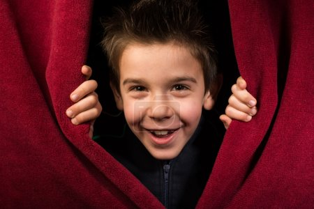 Child appearing beneath the curtain. Red curtain....