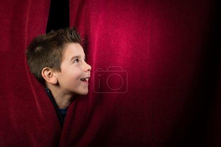 Photo pour Enfant apparaissant sous le rideau. Rideau rouge. - image libre de droit