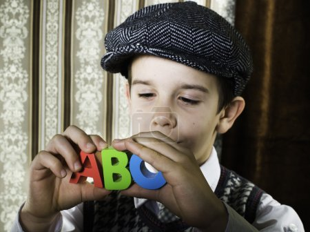 Photo for Child in vintage clothes hold multicolor letters a b c - Royalty Free Image