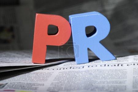 Photo pour Le mot PR sur le journal. Lettres en bois - image libre de droit