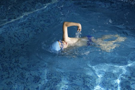 Photo for Child swimmer in swimming pool. Blue color swimming pool - Royalty Free Image