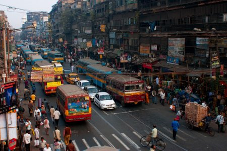 Photo for CALCUTTA, INDIA: Pedestrians cross the road in front of motorcycles, cars and buses at the crossroads. Kolkata has a density of 814.80 vehicles per km road length - Royalty Free Image
