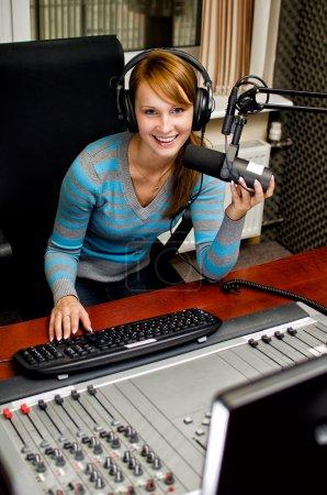 Photo pour Portrait de DJ féminine travaillant devant un microphone à la radio - image libre de droit