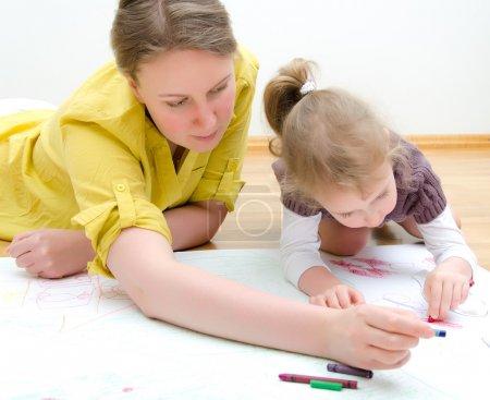 Photo pour Jeune femme et petite fille dessin ensemble assis sur le sol - image libre de droit
