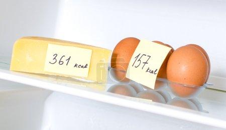 Photo pour Oeufs et fromage avec calories marquées sur le plateau du réfrigérateur - image libre de droit