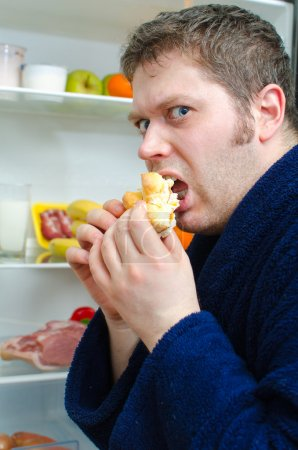 Handsome man eating piece of cake near open fridge