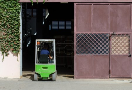Warehouse worker loading boxes by forklift