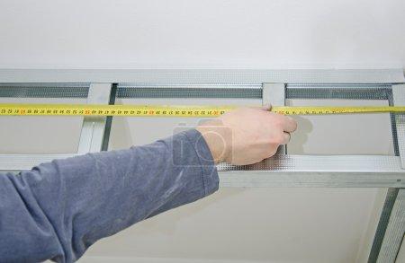 Male hands measuring gypsum plasterboard frame