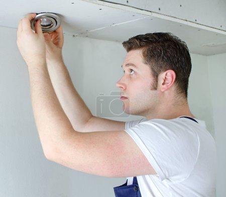Photo pour Électricien certifié installant une ampoule - image libre de droit