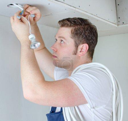 Photo pour Électricien certifié installant la prise pour ampoule - image libre de droit