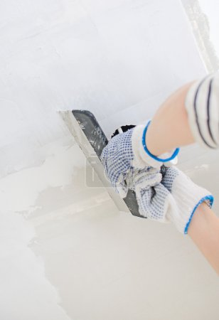 Hand repairs gypsum plasterboard frame with spackling paste