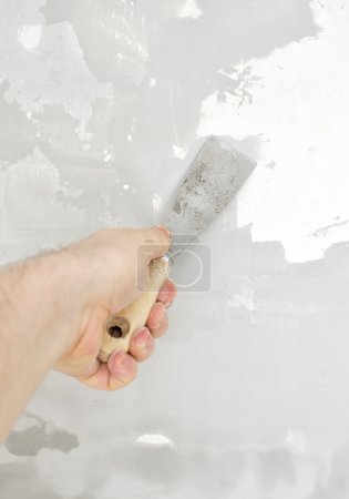 Male hand repairs wall with spackling paste