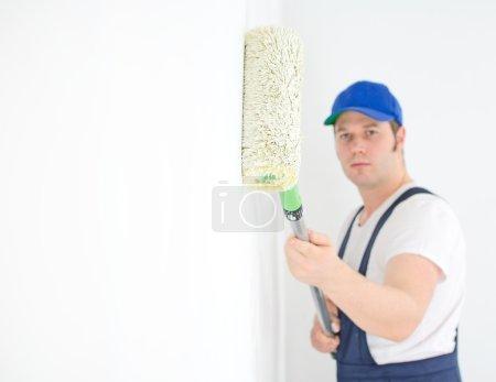 Foto de Pintor en uniforme pinta la pared. Concéntrate en la pintura. Espacio para tu texto . - Imagen libre de derechos