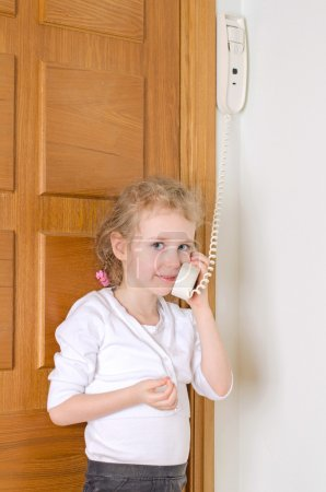 Little girl talking on the intercom at home.