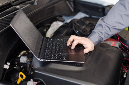 Photo for Mechanic with laptop diagnoses car in workshop. - Royalty Free Image