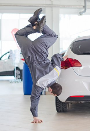 Mechanic having fun in car dealership.
