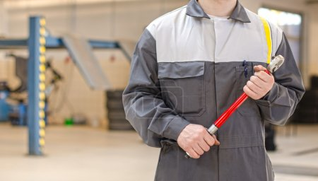 Mechanic with torque wrench at auto repair shop.