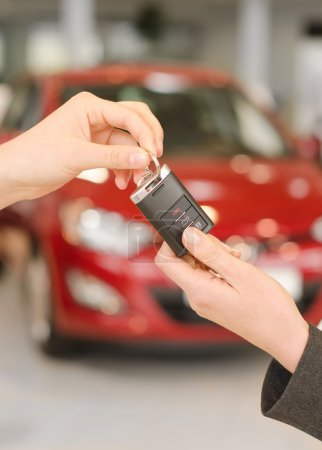 Female hand getting modern car key on a red car background