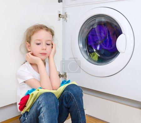 Little girl doing laundry. Housework concept.