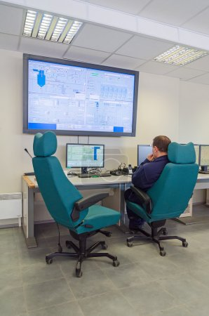 Worker in thermal plant's control room.