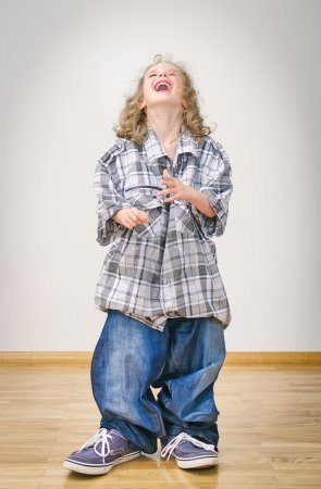Laughing little girl in oversized jeans and shirt.