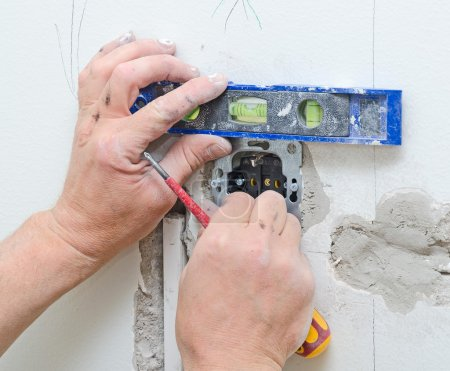 Certified electrician installing socket for light switch.