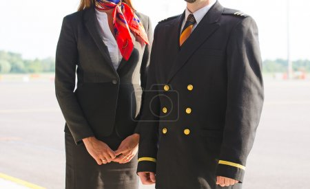 Pilot and stewardess on the airfield.