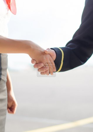 Pilot and stewardess shaking hands on airfield background.