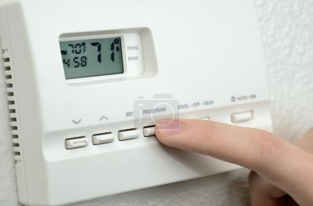 Finger pressing button on digital thermostat...