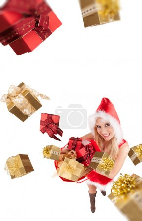 Photo for Attractive young blond woman in santa costume throwing christmas gifts. Studio shot, isolated on white background. Upper gifts are blurred to create motion effect - Royalty Free Image