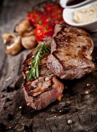 Photo for Delicious beef steaks on wood - Royalty Free Image