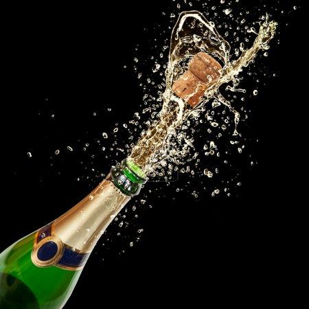 Photo for Celebration theme with splashing champagne, isolated on black background - Royalty Free Image