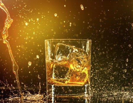 Photo pour Éclaboussures autour d'un verre de whisky - image libre de droit