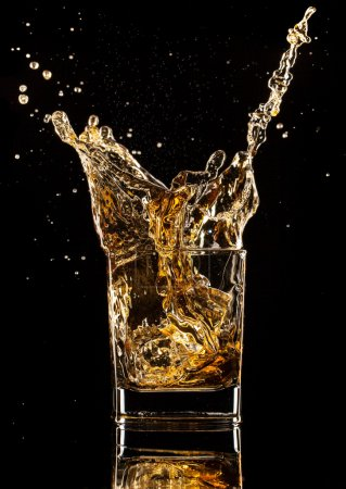 Photo for Concept of glasses of whiskey with splashes, isolated on black background - Royalty Free Image