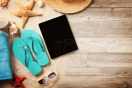 Photo for Upper view on summer swimming accessories with blank tablet on wooden planks - Royalty Free Image