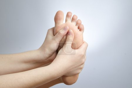 Photo for Pain in the foot. Massage of female feet. Pedicures. Studio shot on a gray background. - Royalty Free Image