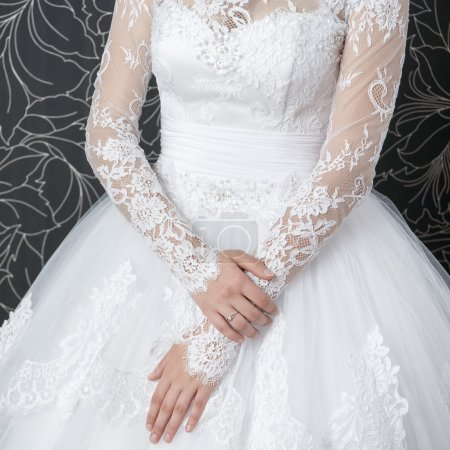 Photo for Lace white wedding dress with long sleeves. Women's hands. - Royalty Free Image