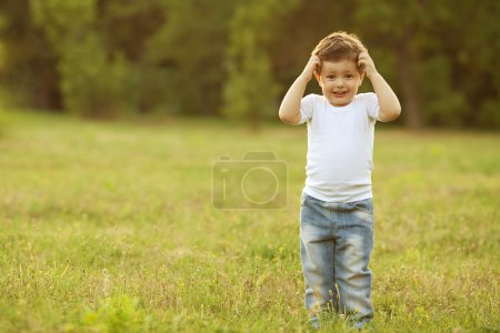 baby boy standing in the meadow
