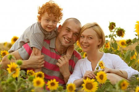 Happy family having fun in the field of sunflowers. Father hugs his son.