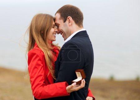 Photo pour Jeune homme romantique proposant à sa petite amie et offrant une bague de fiançailles - image libre de droit