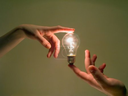 Photo for Electric bulb lighting between human palms - Royalty Free Image