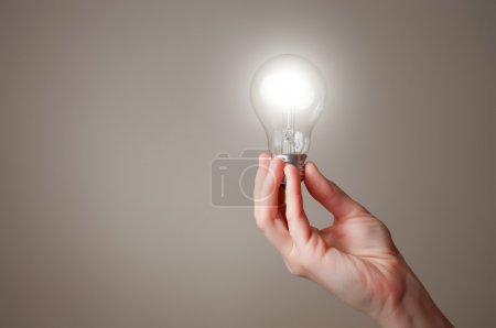 Photo pour Main tenant une ampoule d'éclairage incandescent - image libre de droit